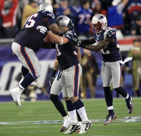 A leaping Vince Wilfork is among the first to congratulate Rob Ninkovich on his third-quarter interception.